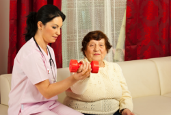caregiver with elderly having light exercise using dumbbell