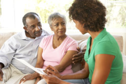 caregiver having conversation with old couple